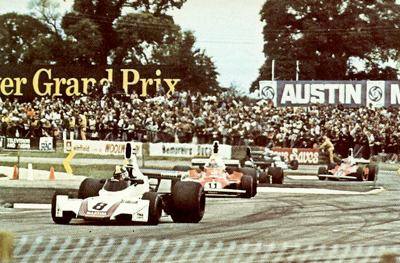 Carlos Pace's Brabham leads a stream of 1975 F1 GP cars through the Woodcote esses